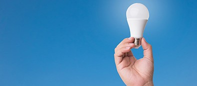 a hand holding a lightbulb against a blue background