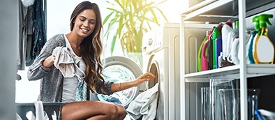 woman smiling and doing laundry