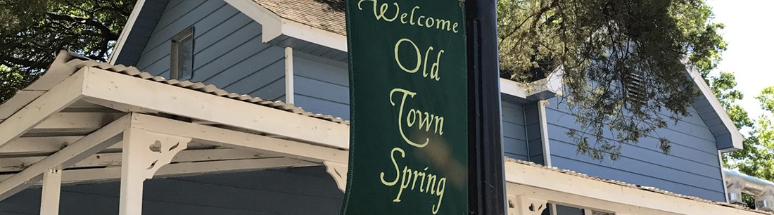 "Old antique wooden home from old town spring with sign in front saying ""welcome to Old Town Spring""."