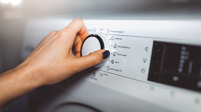 Woman's hand settings dial on washing machine.