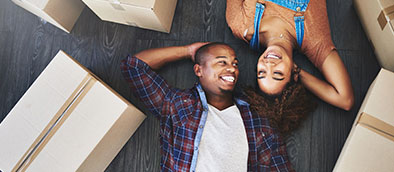 Couple lying next to boxes and smiling