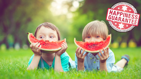 Happy kids eating watermelon on the grass.